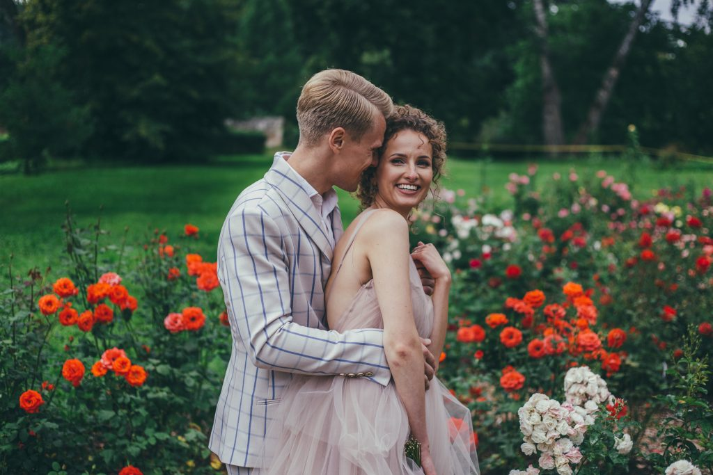 Wedding photography in flower fields and soft color palette. Happy newlyweds couple.